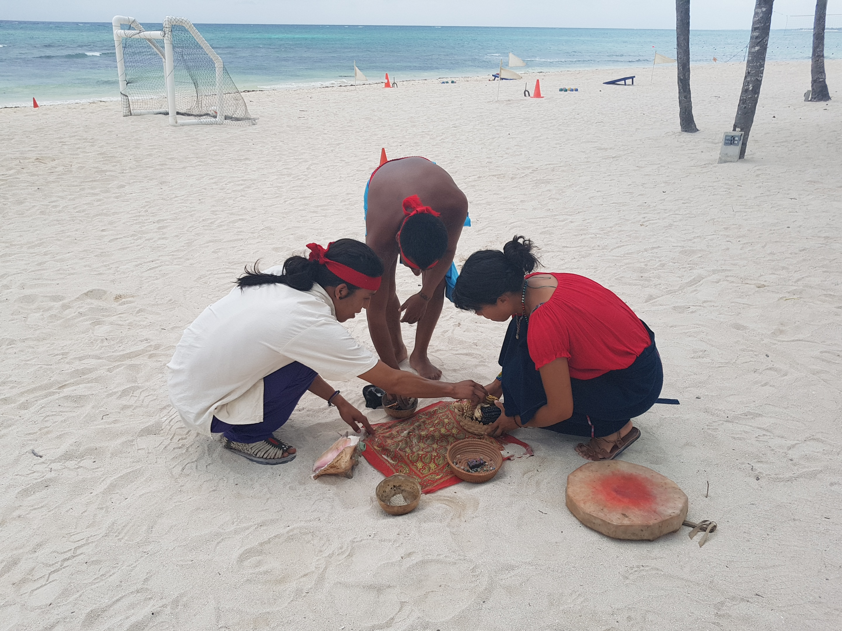 Three shamans at the beach getting tools ready on the sand, a drum , corn shells etc.