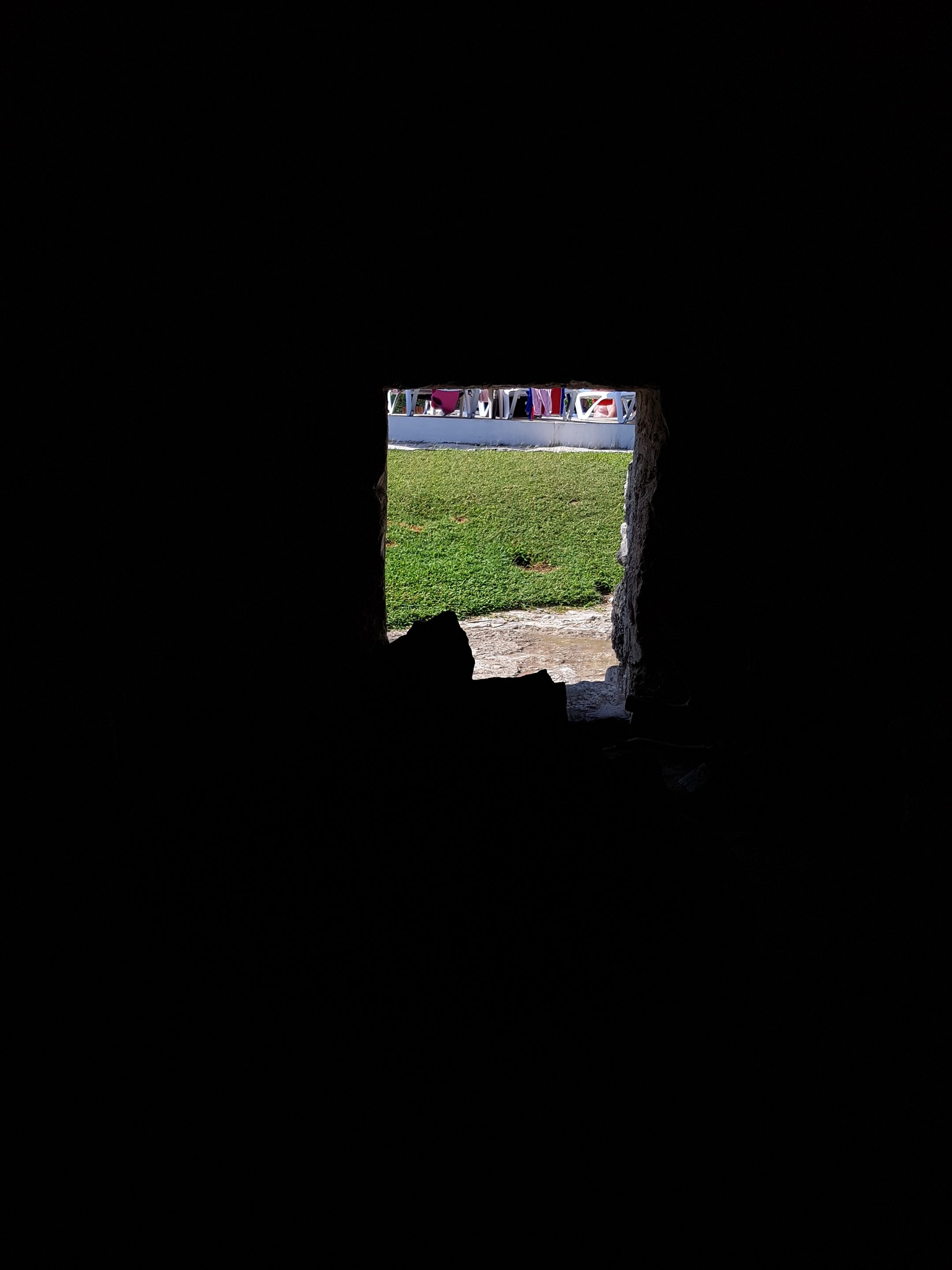 View from inside temazcal , darkness with a small opening showing daylight and grass outside