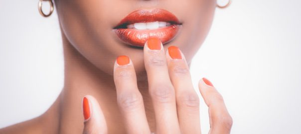 Woman with oragnge lipstic and orange painted nails